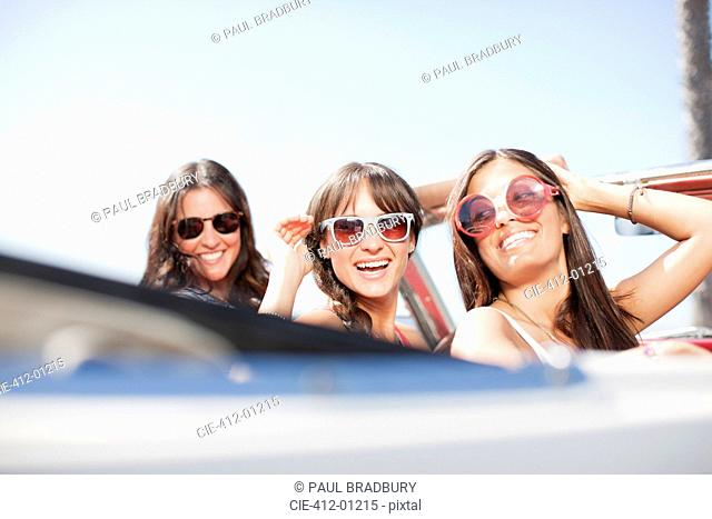 Smiling women driving convertible