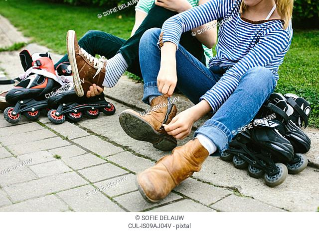 Two sisters sitting on sidewalk unzipping boots for rollerblades