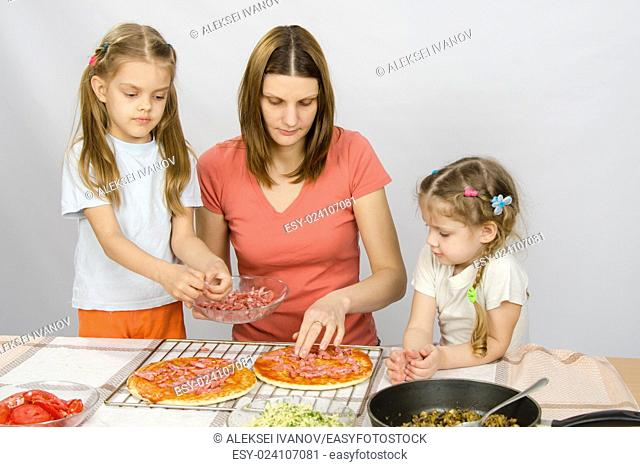 The eldest daughter helps her mother cook a pizza, and the youngest is watching them