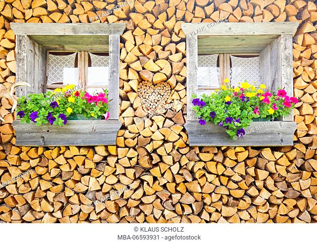 Facade with stacked firewood and flower windows