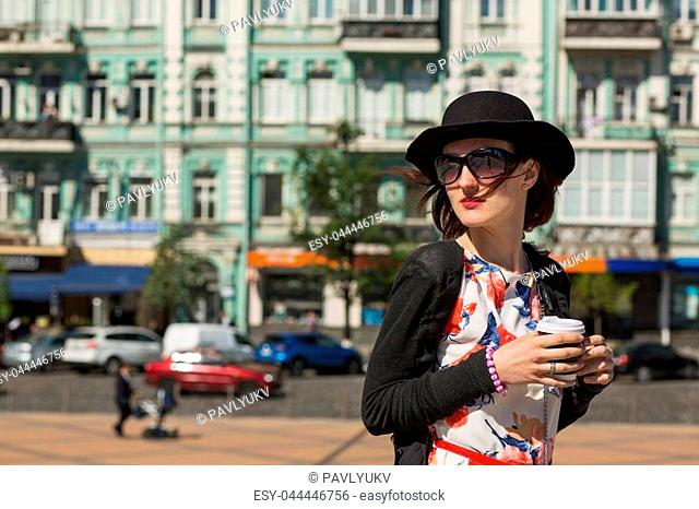 Fashion young model wearing hat and sunglasses drinking morning coffee and walking at the city. Space for text