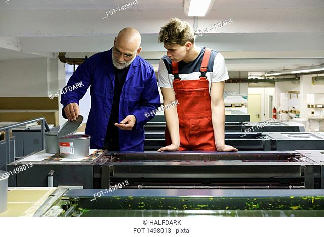 Mature worker showing colleague ink container on printer at printing press