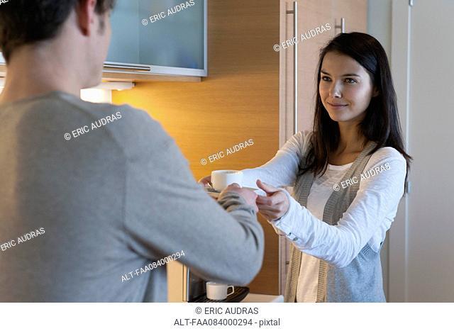 Woman handing man cup of coffee