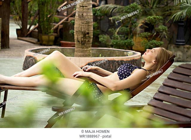 Young woman relaxes on sunlounger, Sepilok, Borneo, Malaysia
