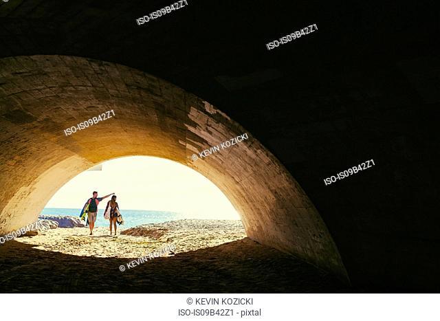Surfing couple walking through beach underpass, Newport Beach, California, USA