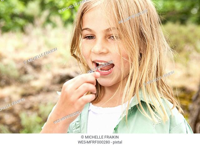 Blond girl eating a blueberry