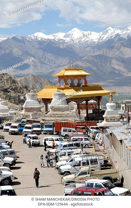 City Chorten white structures and Buddhist temple with snow mountains in background at Leh ; Ladakh ; Jammu & Kashmir ; India