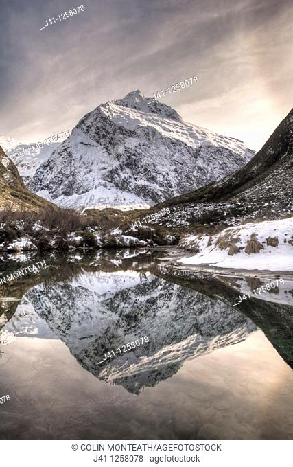 Mt Talbot, winter reflection with ice halo in sky, Hollyford valley, Fiordland National Park, World Heritage site