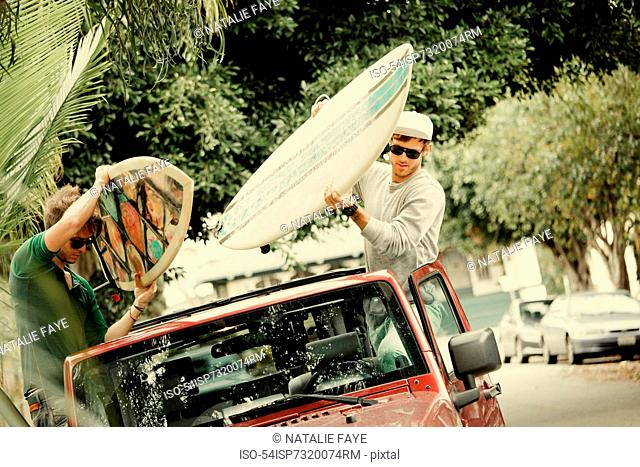 Men tying surfboards to roof of car