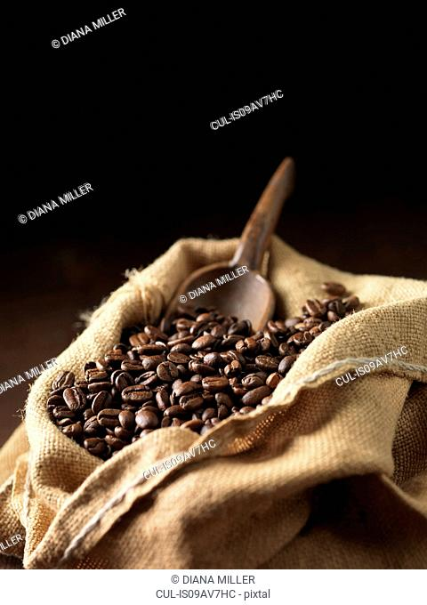 Coffee beans and wooden scoop in woven sack