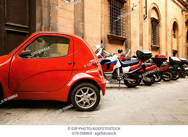 Parked mopeds and miniccar. Florence. Italy
