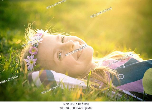 Portrait of smiling little girl lying on meadow wearing flowers