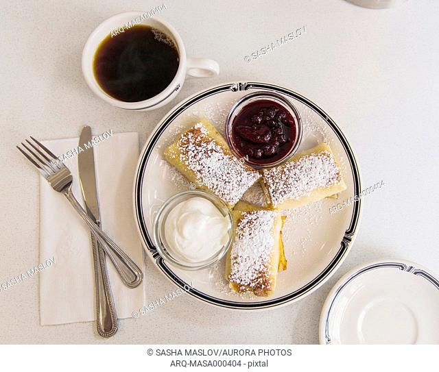 Blintzes and coffee on table