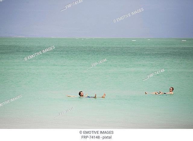 Two men swimming in Dead Sea
