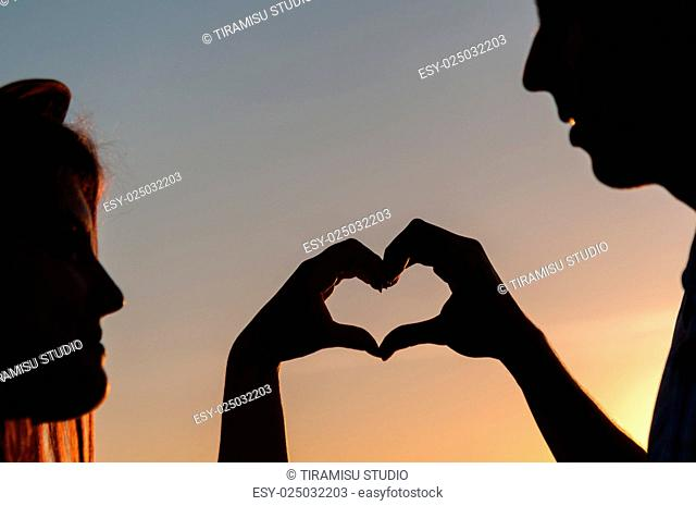 Heart symbol by hands of teenagers silhouette against sunset sky