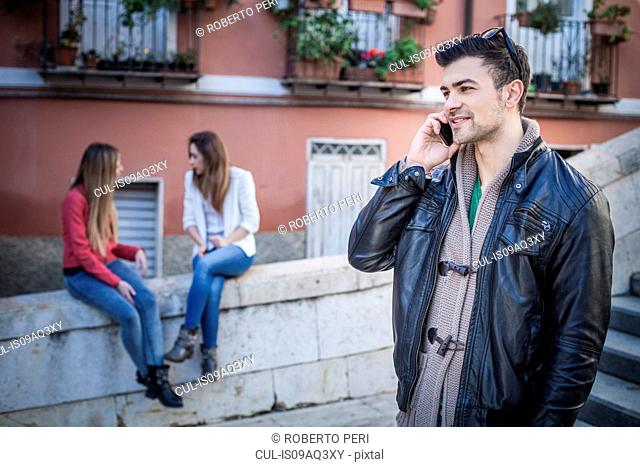 Young man with friends talking on smartphone, Cagliari, Sardinia, Italy