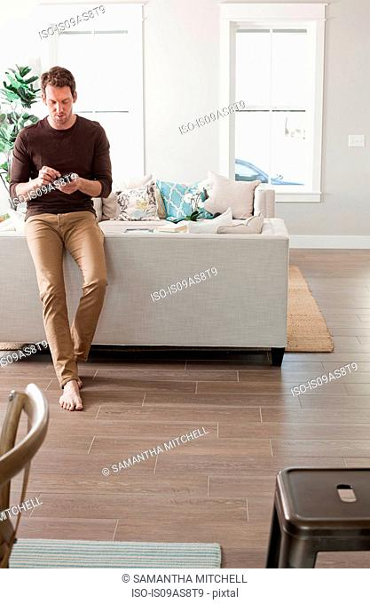 Mid adult man relaxing at home, using smartphone