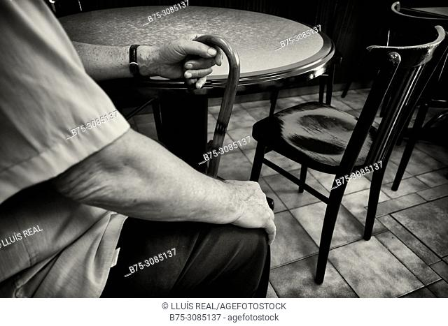 Close up of the hand of a man with a cane seated and rested on a table.Mahon, Menorca, Balearic Islands, Spain