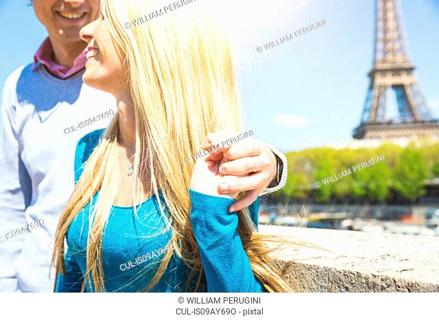 Cropped view of couple in front of eiffel tower smiling, Paris, France