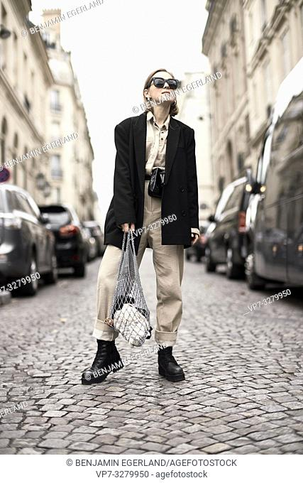 fashionable woman in middle of street in city during fashion week, in Paris, France