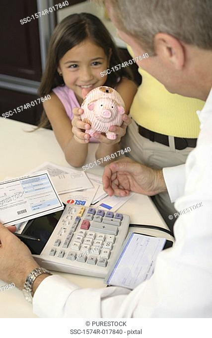 High angle view of a daughter showing a piggy bank to her father
