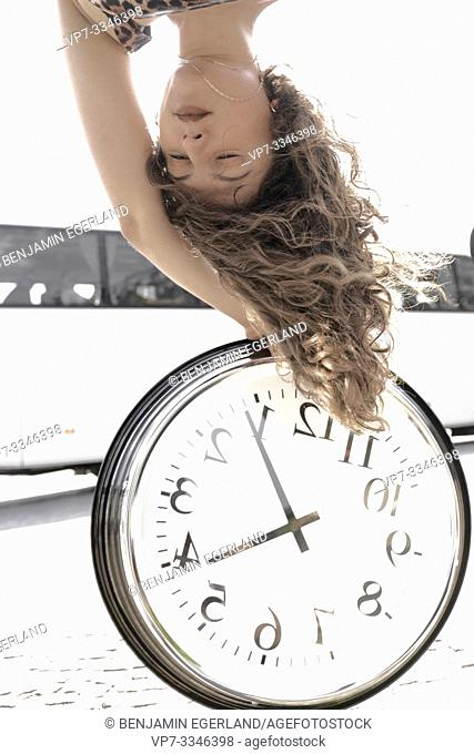young woman upside down with clock at street