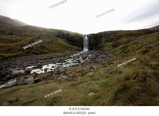 Waterfall and rocky stream in remote field