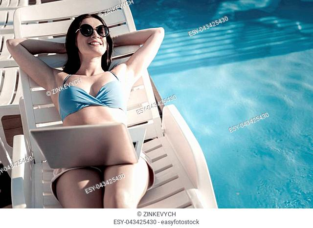 Enjoying my life to the fullest. Top view on a relaxed young lady smiling cheerfully while lying on a sunbed and sunbathing