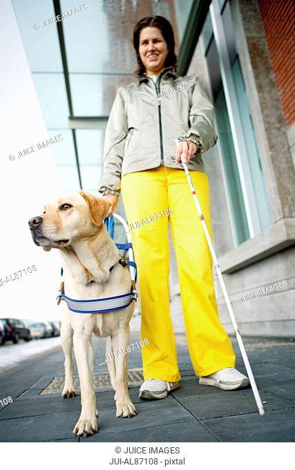 Blind woman and seeing eye dog on sidewalk