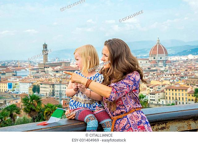 Happy mother pointing baby girl on copy space against panoramic view of florence, italy