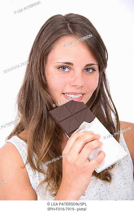 MODEL RELEASED. Young woman eating chocolate