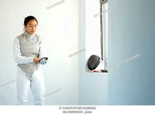 Female fencer pulling on glove