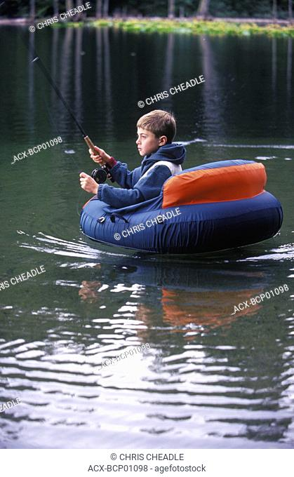 boy fly fishing from float tube in small lake, British Columbia, Canada