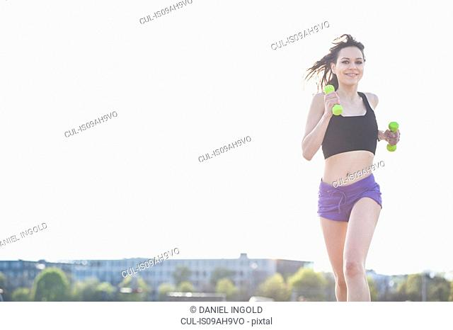 Young woman running carrying dumbbells