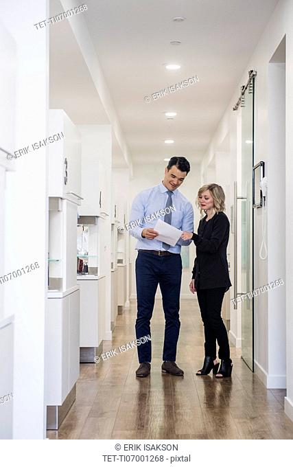 Dentist and dental nurse discussing notes in corridor