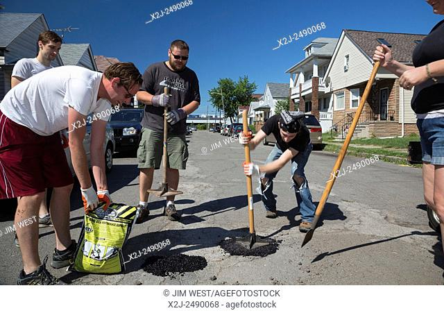 Hamtramck, Michigan - Members of the Hamtramck Guerrilla Road Repair crew fill potholes on the city's streets. Residents acted on their own because the...
