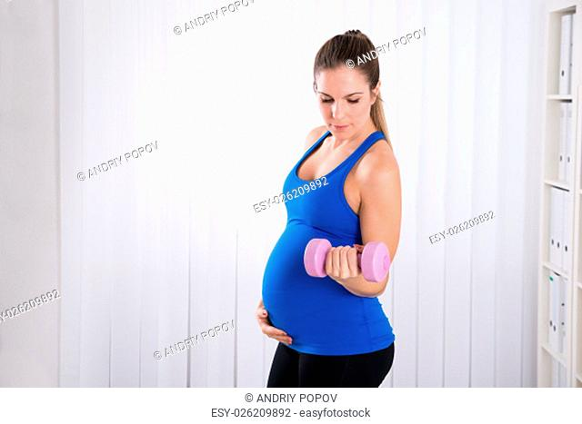 Happy Pregnant Woman Doing Exercise In Sports Hall