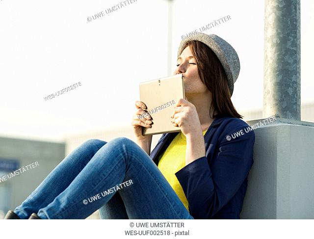 Young woman kissing digital tablet