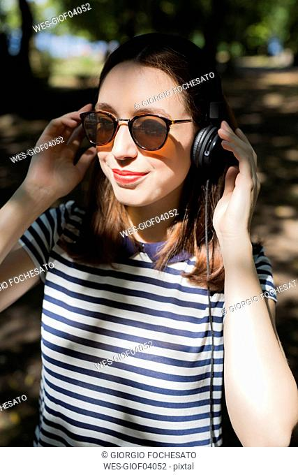Portrait of smiling young woman wearing sunglasses listening music with headphones