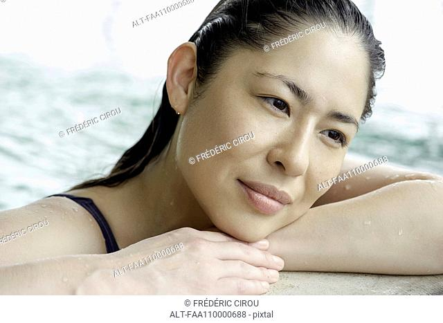 Woman at side of swimming pool resting head on arms