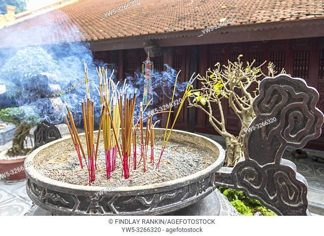 Burning joss sticks for prayer at the Tran Quoc pagoda at Westlake, Hanoi, Vietnam, Asia
