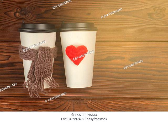 Two cups of coffee to go in white paper cups in sunlight. Morning coffee for couple in love. Knit heart and scarf. Place for text. Toned photo