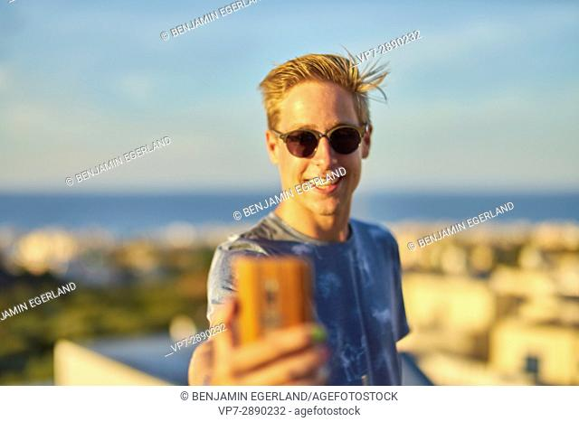 young happy man taking selfie during sunset in holiday destination Hersonissos, Crete, Greece