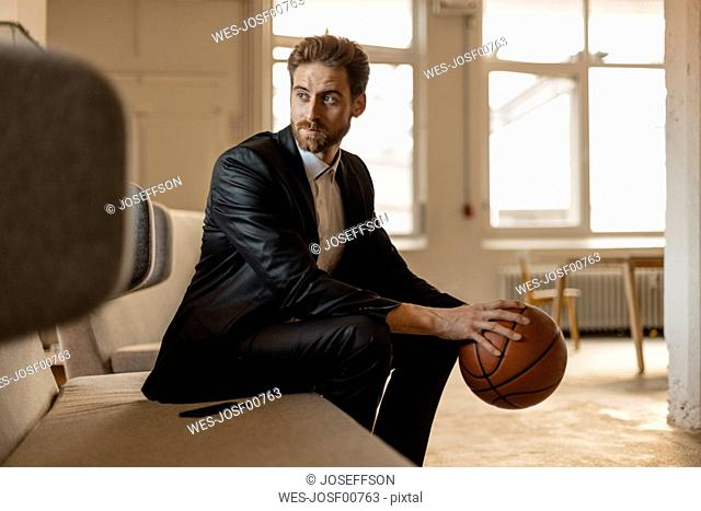 Portrait of young businessman with basketball sitting on the couch in a loft