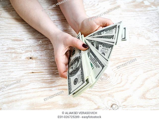 Cash in hands. Pile of one hundred dollar bills. Stack of dollars in hands. Woman counting money. Dollars in hands. Fake money in hands