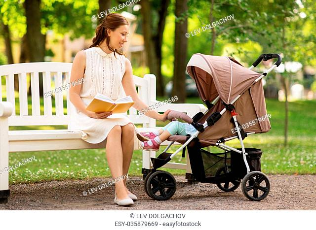 family, motherhood and people concept - happy mother with child in stroller reading book at summer park