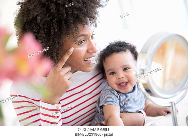 Mother holding baby son applying face cream in mirror