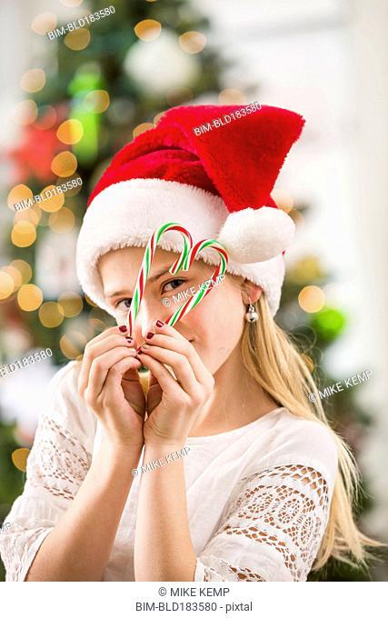 Caucasian girl peering through Christmas candy canes