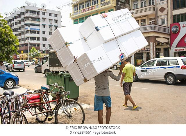 A young man carrying a big thing. Lanmadaw Township, Yangon, Myanmar