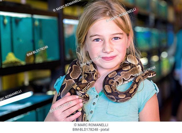Caucasian girl holding snake in pet store